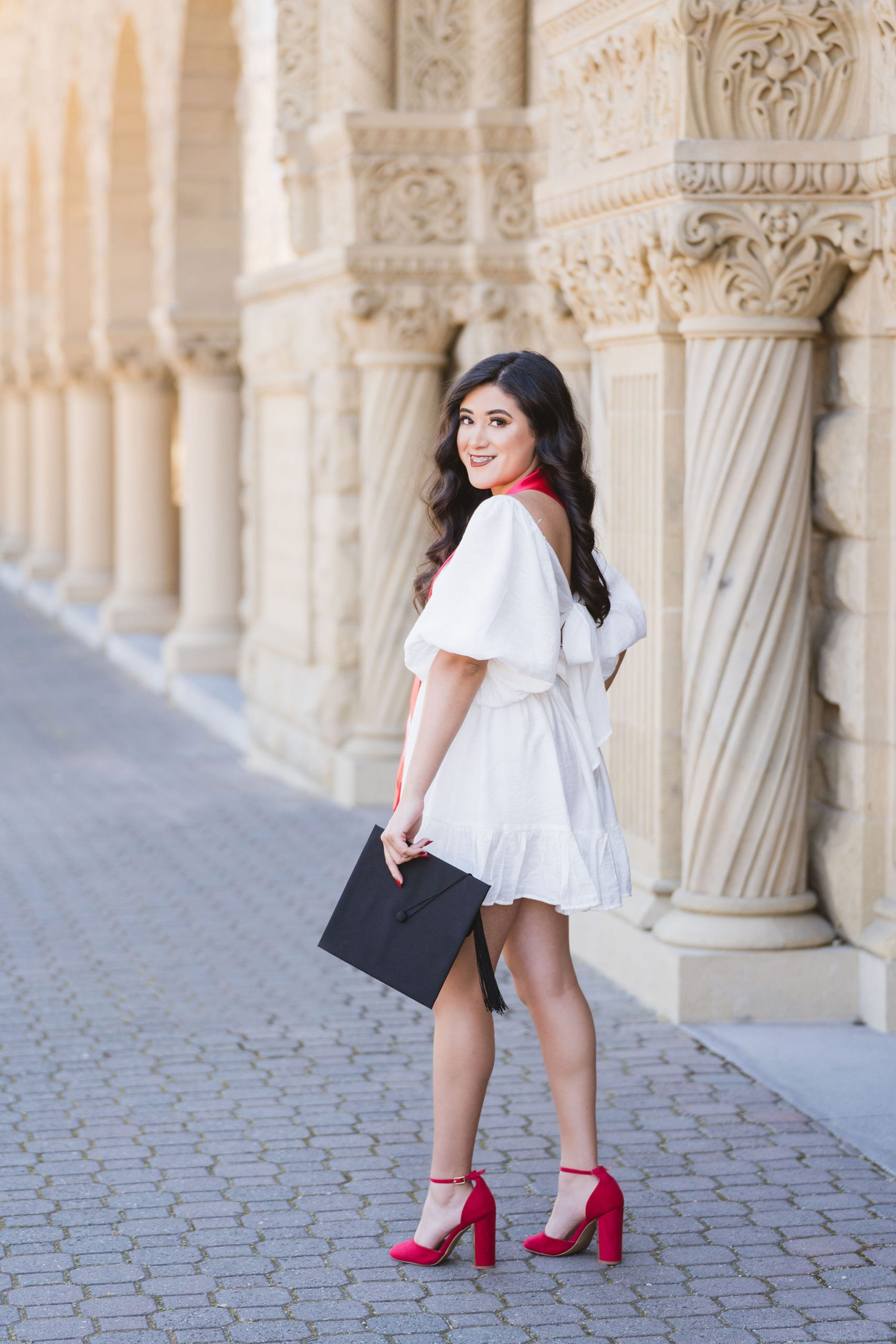 college graduate in white dress in front of stanford university
