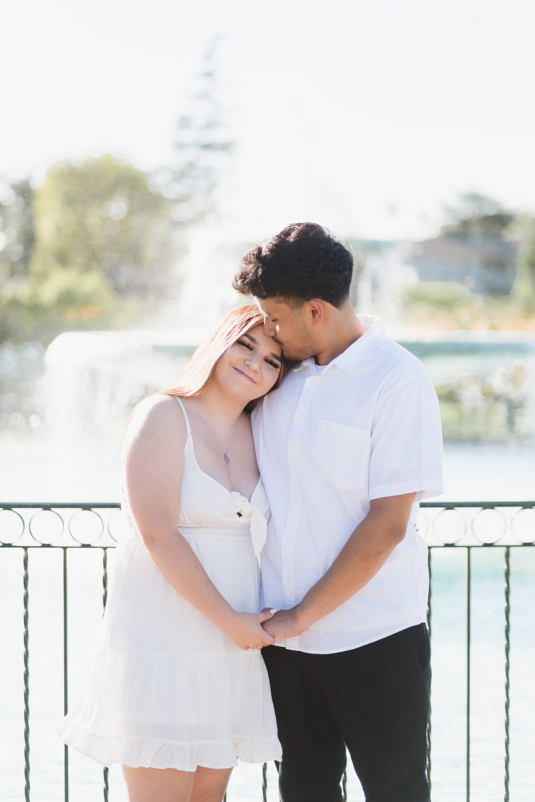boyfriend and girlfriend hugging in front of fountain
