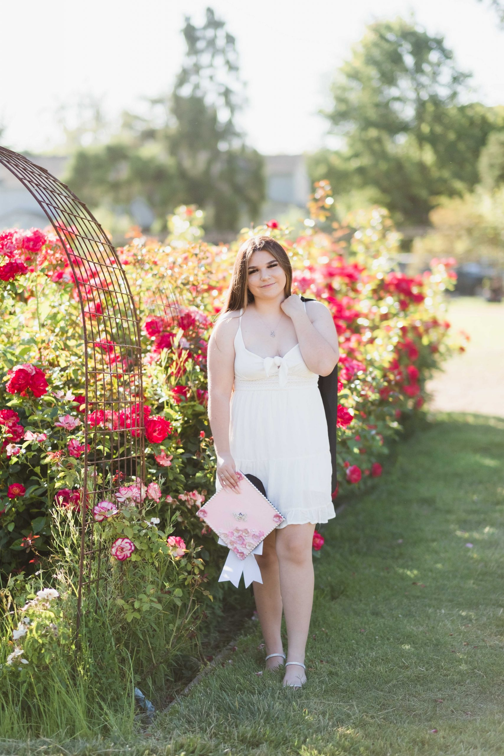 high school graduate in white dress in front of a row of lush red roses