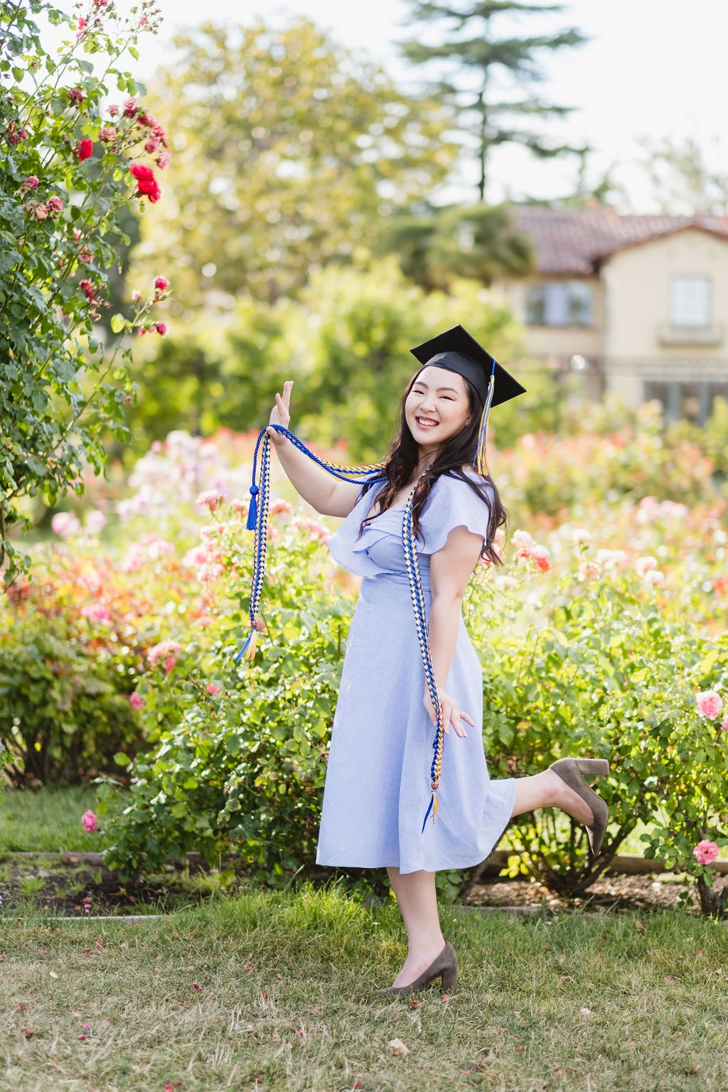 Graduate Holding Honor Society Ropes and Smiling