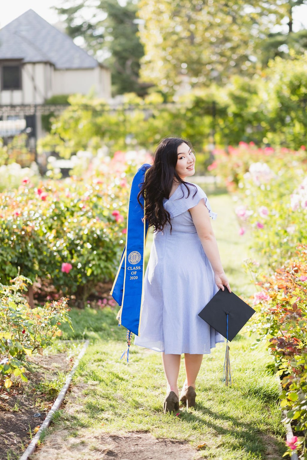 Graduate standing in a path of pink roses