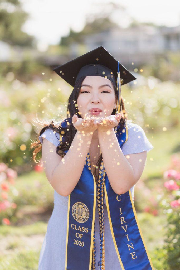 Graduate blowing glitter