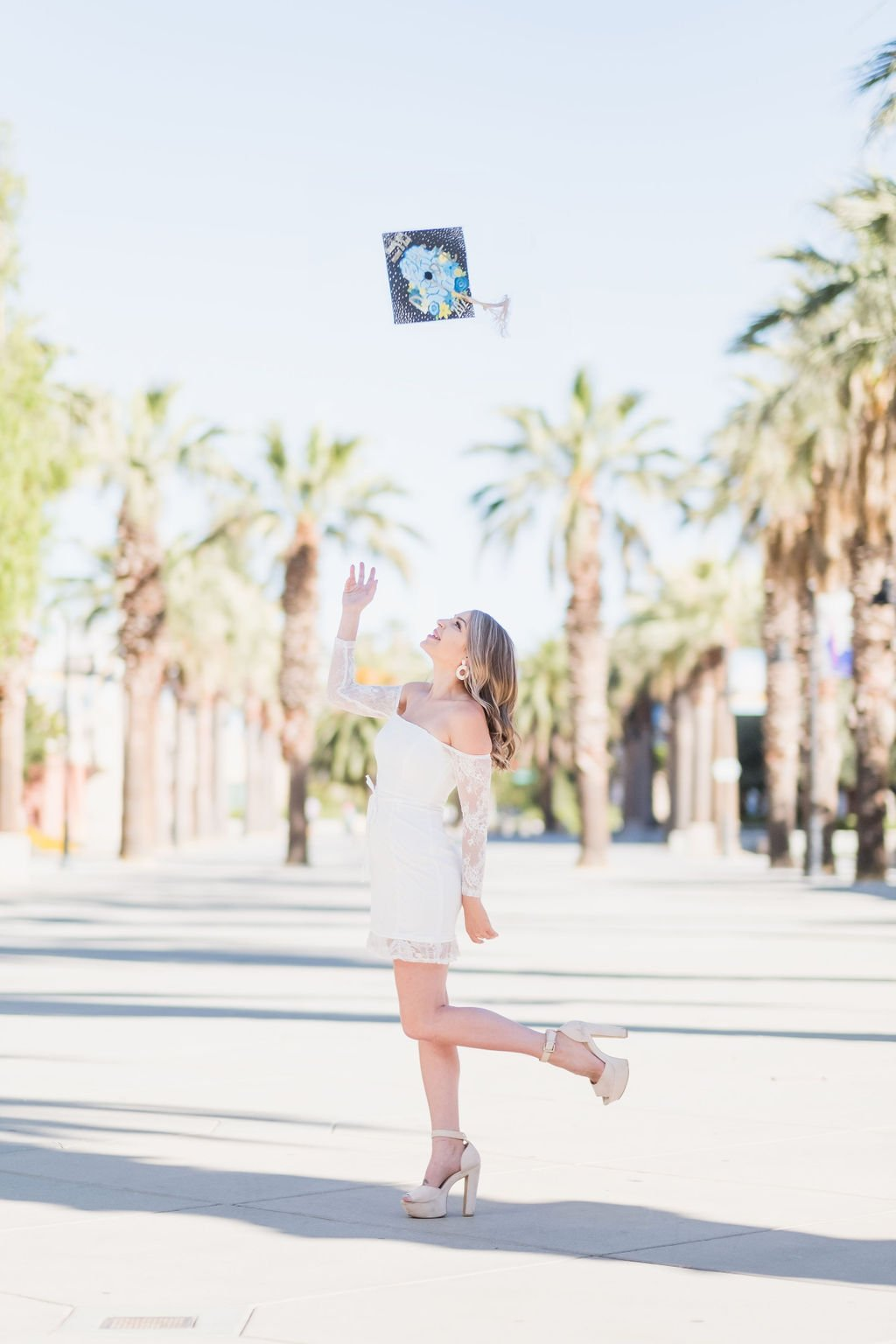 female graduate throwing grad cap in the air at San Jose State