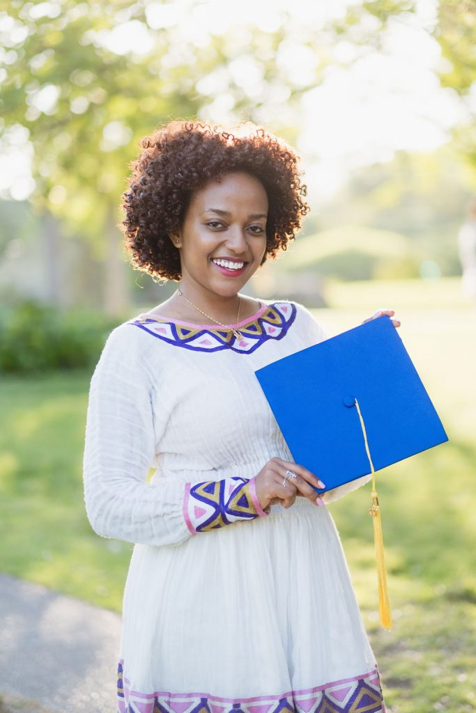 graduate holding her blue graduation cap
