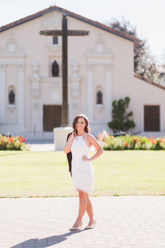 Graduate Posing in Front of Santa Clara University