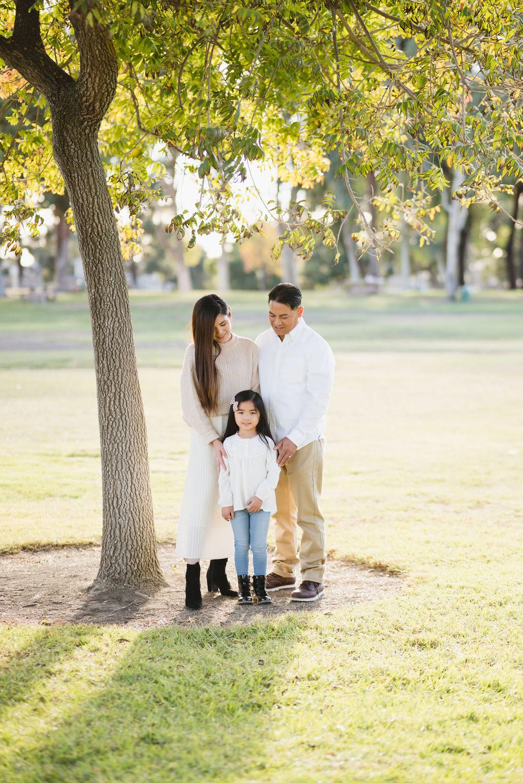 family standing under lush green tree