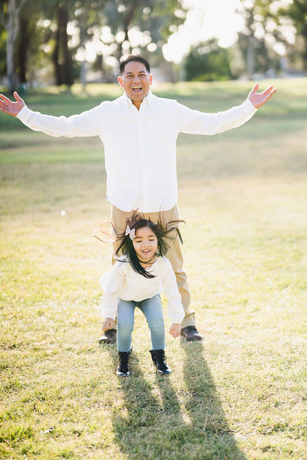 little girl jumping around her father