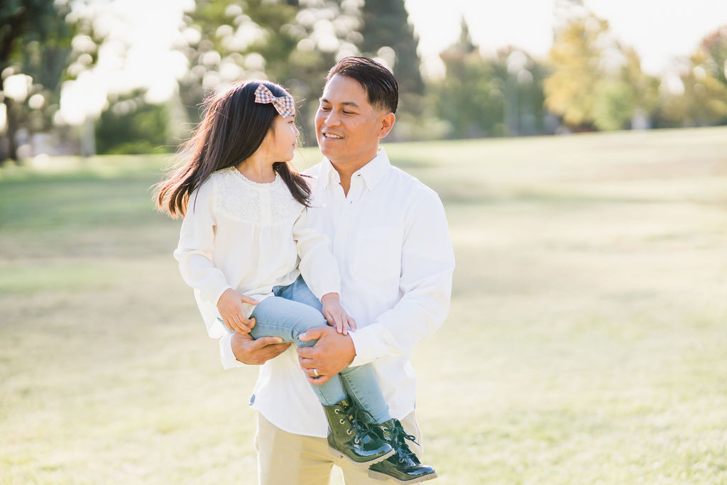 dad holding his daughter in front of grassy field