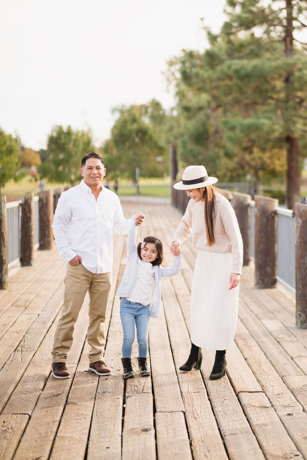 family lifting daughter up on a bridge