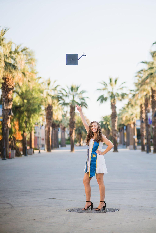 Woman throwing graduation cap in air