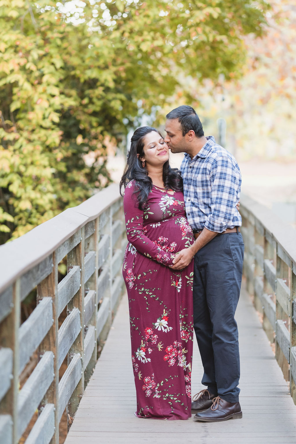 husband kissing his pregnant wife on a rustic bridge