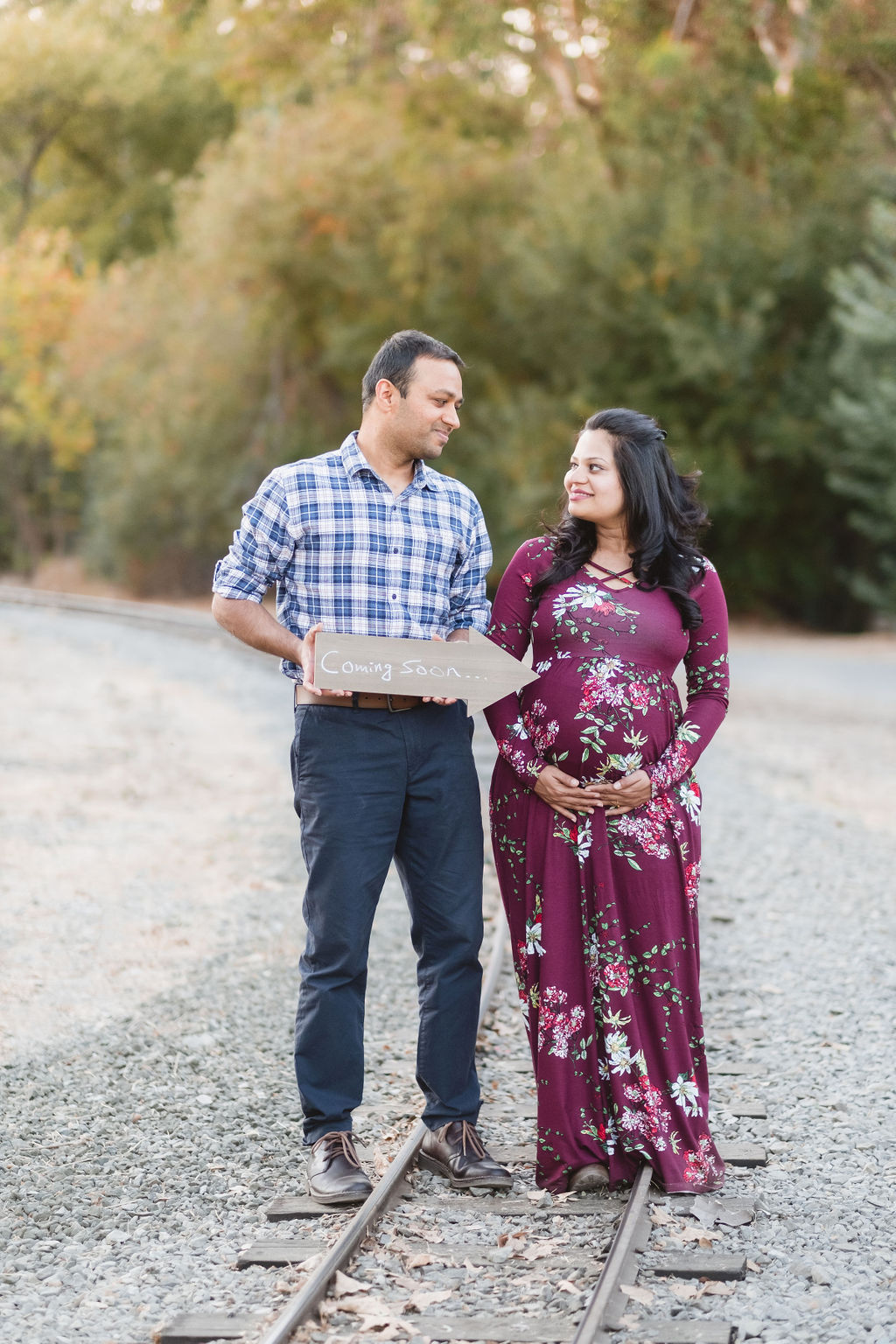 man holding sign next to pregnant wife