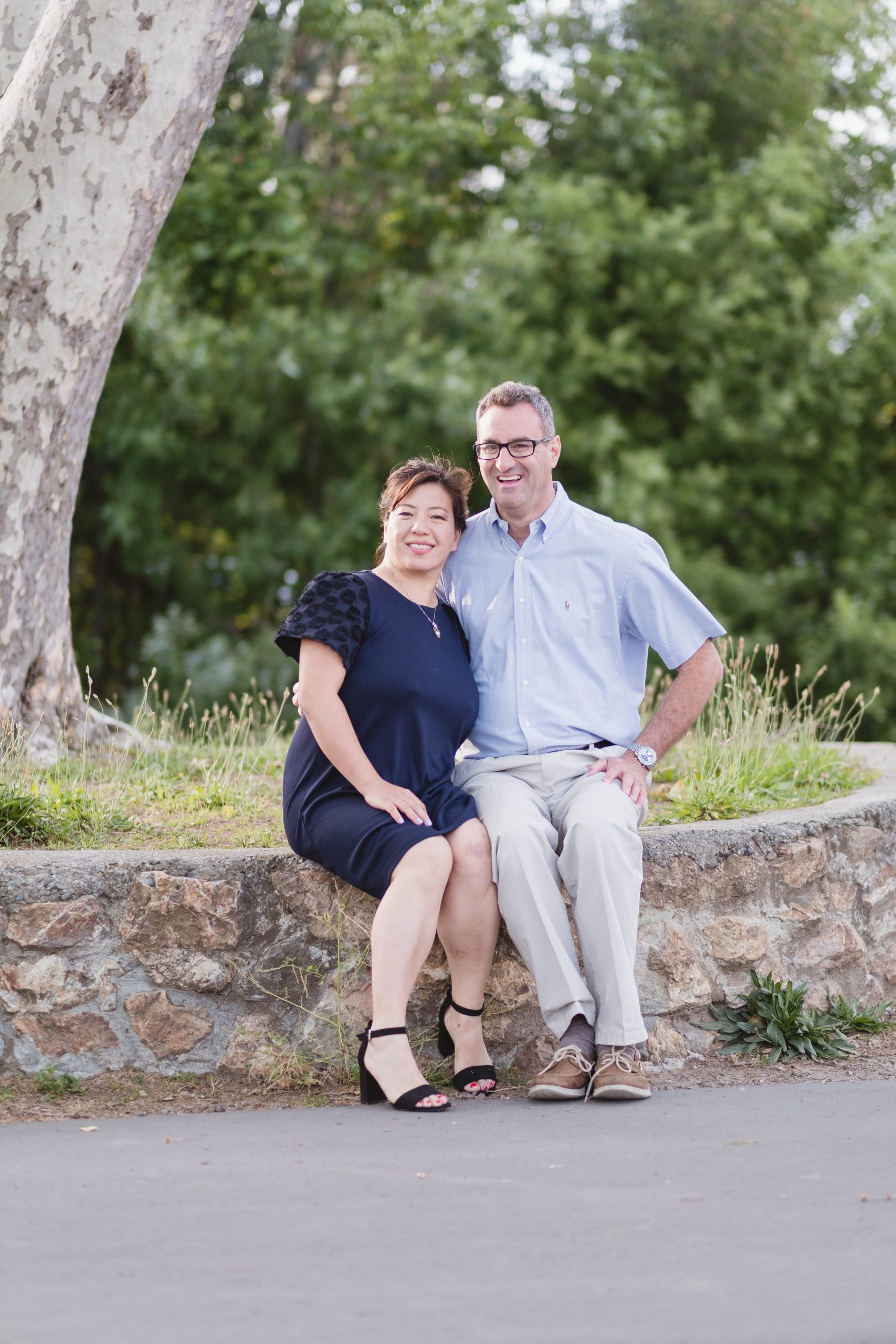 wife and husband sitting on a stone path