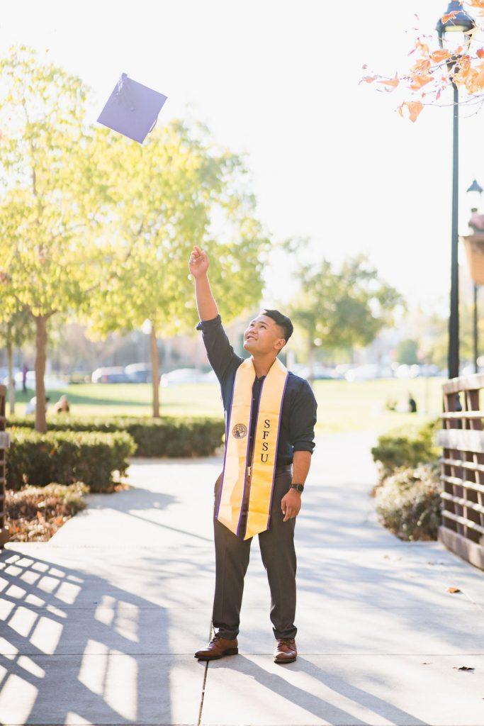 SFSU graduate throwing his grad cap in the air
