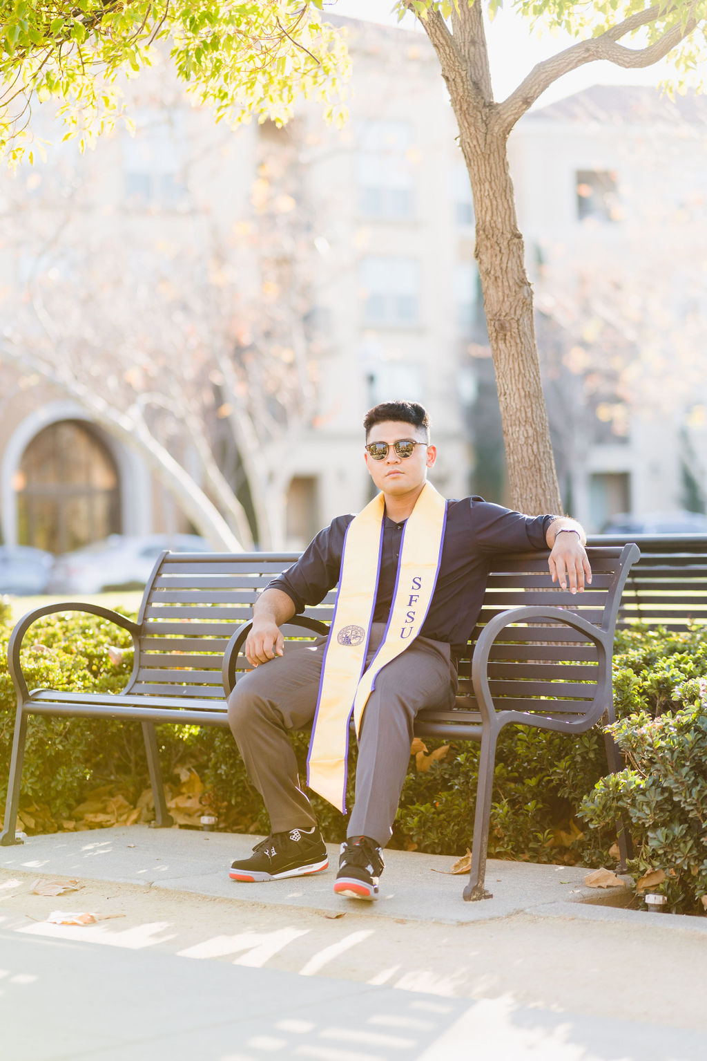 Male College Graduate relaxing on park bench