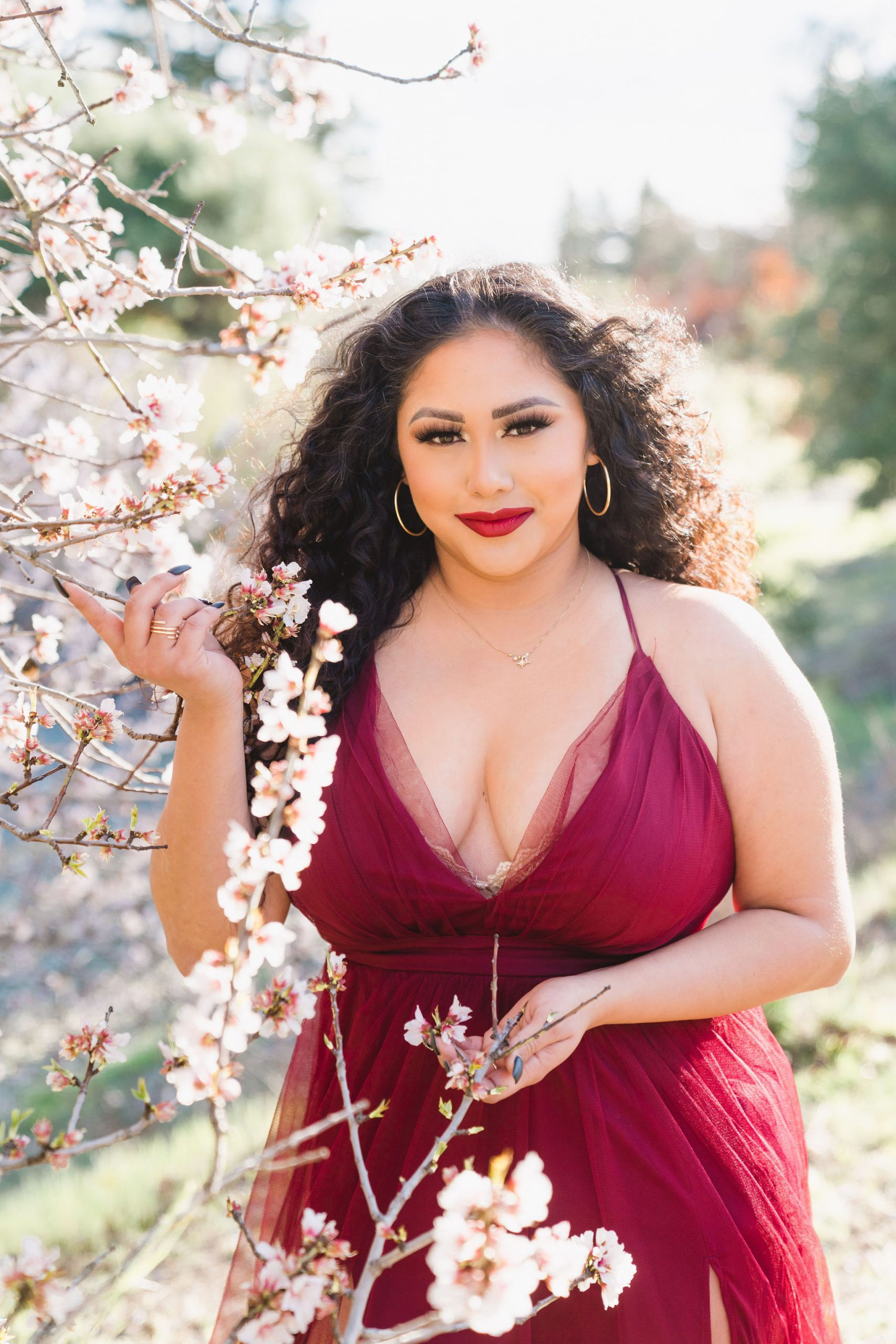 woman in red dress holding cherry blossoms in san jose