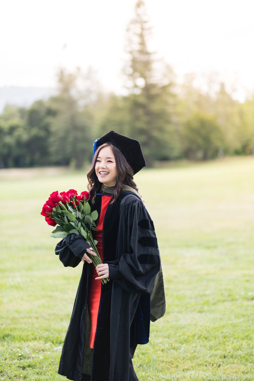 college graduate holding bouquet of red roses
