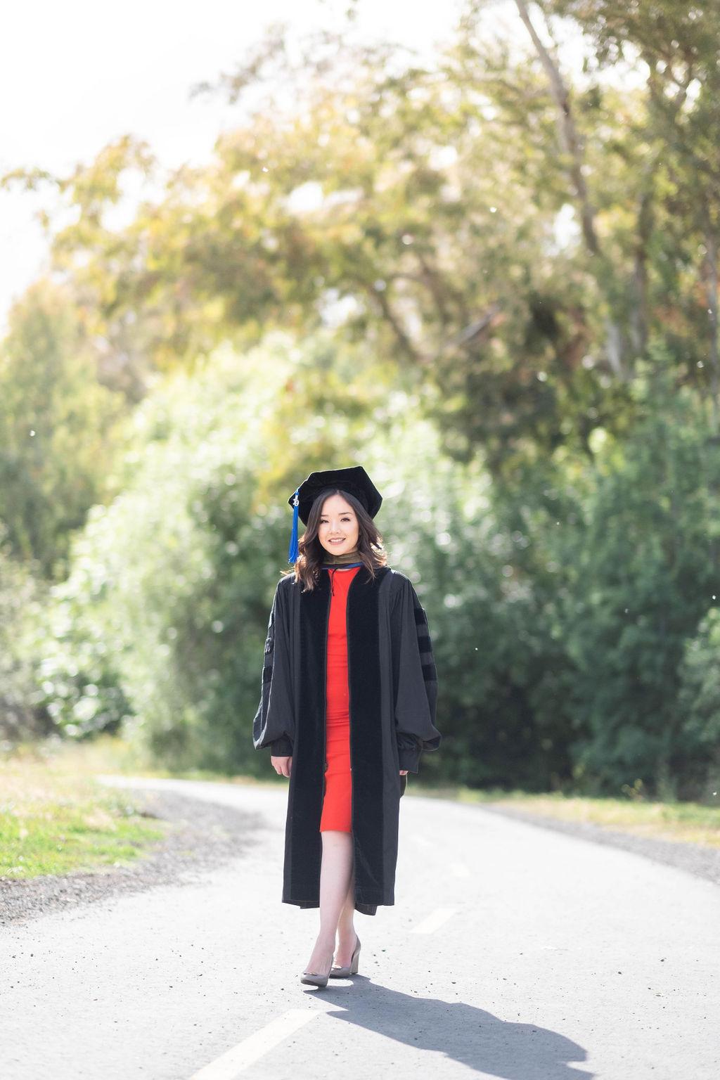 college graduate walking along vasona lake park pathway
